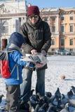 St. PETERSBURG, RUSSLAND - 5. MÄRZ: Das Kind mit der Vaterzufuhr eine Taube von den Händen RUSSLAND - 5. MÄRZ 2017 Stockbild