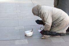 ST PETERSBURG, RUSSLAND - 24. MÄRZ: Der arme Mann auf der Straße von St Petersburg am 24. März 2016 Lizenzfreie Stockbilder