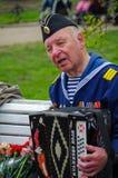St. PETERSBURG, RUSSLAND - 9. MAI 2014: angenehmer Veteran spielt Akkordeon auf dem 69. Jahrestag des Sieges im Zweiten Weltkrieg Lizenzfreies Stockfoto