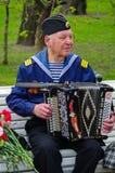 St. PETERSBURG, RUSSLAND - 9. MAI 2014: angenehmer Veteran spielt Akkordeon auf dem 69. Jahrestag des Sieges im Zweiten Weltkrieg Stockbilder