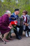 St. PETERSBURG, RUSSLAND - 9. MAI 2014: angenehmer Veteran spielt Akkordeon auf dem 69. Jahrestag des Sieges im Zweiten Weltkrieg Stockfotografie