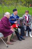 St. PETERSBURG, RUSSLAND - 9. MAI 2014: angenehmer Veteran spielt Akkordeon auf dem 69. Jahrestag des Sieges im Zweiten Weltkrieg Lizenzfreie Stockfotografie