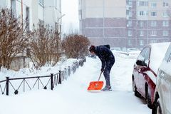 St Petersburg Ryssland - Januari 17, 2019: En man gör ren insnöat gården med en skyffel efter ett tungt snöfall royaltyfri foto