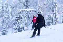 St Petersburg Ryssland-Januari 27, 2019: Snö-täckt skidar lutningen i bergen med en skidlift och skidåkningskidåkare fotografering för bildbyråer