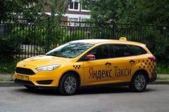 St Petersburg Ryssland - Juli 08, 2017: Den gula taxiföretagsYandex-taxien erbjuder klienterna Royaltyfri Fotografi