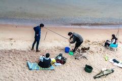 St Petersburg Ryssland - Juli 10, 2018: Gruppen av fiskare fiskar på de sandiga kusterna av golfen av Finland under bron royaltyfri bild