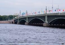 ST PETERSBURG RYSSLAND - JULI 28, 2017: Treenighetbron dekorerade med flaggor i heder av den ryska marinen Royaltyfri Foto