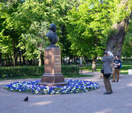 St Petersburg Ryssland - Juni 02, 2016: den äldre mannen fotograferar bysten av den stora kompositören Glinka Royaltyfri Fotografi