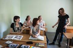St Petersburg Ryssland - Juni 10, 2018: Ger läraren för det utländska språket för den unga kvinnan i ett litet klassrum studenter royaltyfria bilder