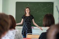 St Petersburg Ryssland - Juni 10, 2018: Kurs för spanskt språk på delstatsuniversitetet Läraren i en gest kastar upp hans händer royaltyfri foto