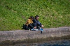 ST PETERSBURG RYSSLAND, 02 MAJ 2018: Familj i gränsen av den Moika floden under en ursnygg solig dag i St Arkivfoton