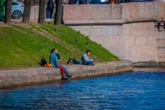 ST PETERSBURG RYSSLAND, 02 MAJ 2018: Familj i gränsen av den Moika floden under en ursnygg solig dag i St Royaltyfria Bilder