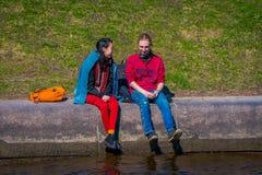 ST PETERSBURG RYSSLAND, 02 MAJ 2018: Familj i gränsen av den Moika floden under en ursnygg solig dag i St Arkivfoto