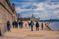 ST PETERSBURG RYSSLAND, 17 MAJ 2018: Folk som går i stranden av Peter och Paul Fortress i StPetersburg på molnet Royaltyfria Foton