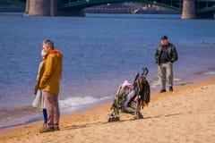 ST PETERSBURG RYSSLAND, 17 MAJ 2018: Folk som går i stranden av Peter och Paul Fortress i StPetersburg på molnet Arkivfoto