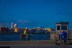 ST PETERSBURG RYSSLAND, 01 MAJ 2018: Oidentifierat folk som cyklar i trottoaren på flodstranden av fontankafloden med något Royaltyfri Fotografi