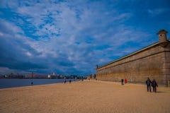 ST PETERSBURG RYSSLAND, 17 MAJ 2018: Oidentifierat folk som går över den gula sanden i stranden av Peter och Paul Royaltyfria Bilder