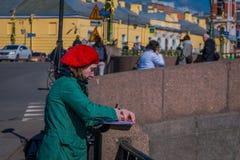 ST PETERSBURG RYSSLAND, 02 MAJ 2018: Slut upp av den blonda kvinnan som bär ett svart omslag för solglasögonans-svart och att gå  Arkivbild