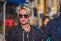 ST PETERSBURG RYSSLAND, 02 MAJ 2018: Slut upp av den blonda kvinnan som bär ett svart omslag för solglasögonans-svart och att gå  Arkivbilder