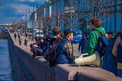 ST PETERSBURG RYSSLAND, 01 MAJ 2018: Utomhus- sikt av oidentifierat folk som nästan sitter i en gräns på flodstranden a Royaltyfri Bild