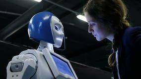 St Petersburg Ryssland - November 12, 2018: Flicka som talar till en humanoid robot arkivfilmer