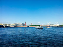 St. Petersburg view on Neva river. View of the spit of Vasilievsky island and rostralnie columns. Blue water of the river Neva and white pleasure boats Stock Photos