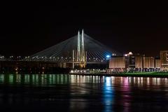 St- Petersburgnachtansicht der Brücke und der Stadt beleuchtet über dem Fluss Lizenzfreie Stockbilder