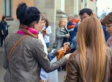 ST PETERSBURGO, RÚSSIA - 8 de maio de 2015: Distribuição de fitas de St George na véspera de Victory Day aos transeuntes exterior foto de stock