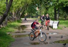 ST Petersburgo, Rússia A família por bicicletas vai em um trajeto do parque Foco na mulher Foto de Stock