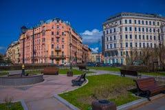 ST PETERSBURGO, RÚSSIA, O 1º DE MAIO DE 2018: Veja cadeiras públicas de madeira do od em um parque com as construções enormes enc Fotos de Stock
