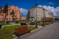 ST PETERSBURGO, RÚSSIA, O 1º DE MAIO DE 2018: Veja cadeiras públicas de madeira do od em um parque com as construções enormes enc Foto de Stock Royalty Free