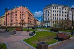 ST PETERSBURGO, RÚSSIA, O 1º DE MAIO DE 2018: Veja cadeiras públicas de madeira do od em um parque com as construções enormes enc Fotografia de Stock