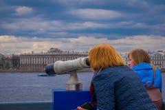 ST PETERSBURGO, RÚSSIA, O 17 DE MAIO DE 2018: Opinião exterior os povos não identificados que usam uma máquina do visor dos binóc Imagens de Stock Royalty Free