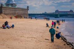 ST PETERSBURGO, RÚSSIA, O 17 DE MAIO DE 2018: Povos que andam na praia de Peter e de Paul Fortress em StPetersburg na nuvem Fotos de Stock Royalty Free