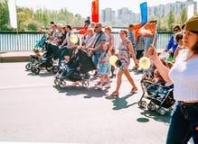 ST PETERSBURGO, RUSIA - 9 DE MAYO DE 2016: Familias jovenes con los cochecitos en las filas de la procesión festiva en Victory Da Fotografía de archivo libre de regalías