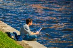 ST PETERSBURGO, RUSIA, EL 2 DE MAYO DE 2018: Hombre no identificado que se sienta en la frontera del río de Moika que lee un libr Imagen de archivo libre de regalías