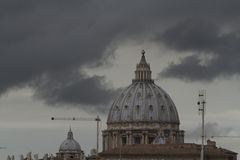 St Pietro. The roof tops of Rome with the Dome of the basillica , cranes and very dark grey skies royalty free stock image