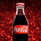 St PIETROBURGO, RUSSIA - 8 DICEMBRE 2014: Bottiglia classica di Coca-Cola sul fondo rosso di scintillio Immagini Stock Libere da Diritti