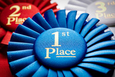 1st place winners rosette or badge. 1st place blue winners rosette or badge to be awarded as a prize to the winner of a competition made of pleated blue ribbon stock photography