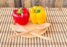 Söt röd och gul peppar i träplatta Royaltyfria Foton