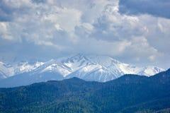 St?rmischer Himmel ?ber schneebedeckten felsigen Bergen Gewitterwolken ?ber schneebedeckten Bergen stockbild