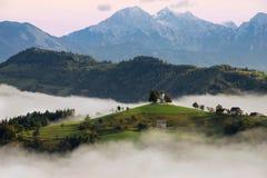 St Thomas bergkyrka i Slovenien i en dimmig soluppgång Arkivfoto