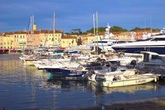 ST TROPEZ, ФРАНЦИЯ, 4-ОЕ ИЮНЯ 2016: Современные шлюпки в гавани перед традиционными домами Провансали стоковое изображение