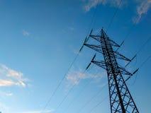 St?ttar h?g-sp?nning kraftledningar mot den bl?a himlen med moln elektrisk industri arkivbild