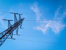 St?ttar h?g-sp?nning kraftledningar mot den bl?a himlen med moln elektrisk industri arkivfoton
