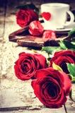 St-valentin inställning med kaffekoppen och röda rosor Fotografering för Bildbyråer