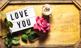 St. Valentine's Day greeting. Top view composition greeting for St. Valentine& x27;s Day for a woman with a cup of cappuccino with heart, a rose and a word Royalty Free Stock Images
