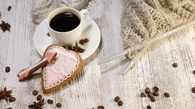 St. Valentine Day background. A cup of coffee and ginger biscuit, knitting needle and yarn are on wooden background. Hand puts arrow shaped bisciut 4k stock video