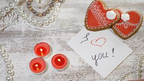 St. Valentine Day background. Two heart shaped ginger biscuits, tea candles and pearl beads on wooden background. Female. Hand puts I love You message note stock video footage