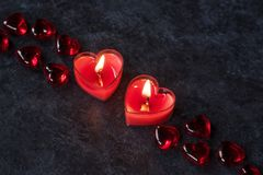 St Valentine day decor. Two red heart shaped candles, St Valentine day decor at the dark background stock photo